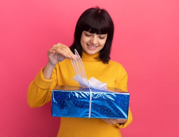 Довольная молодая брюнетка кавказская девушка держит и смотрит на подарочную коробку, изолированную на розовой стене с копией пространства