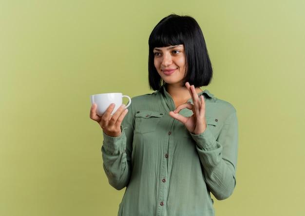 La giovane ragazza caucasica castana soddisfatta tiene il segno giusto della mano di gesti e della tazza che esamina il lato