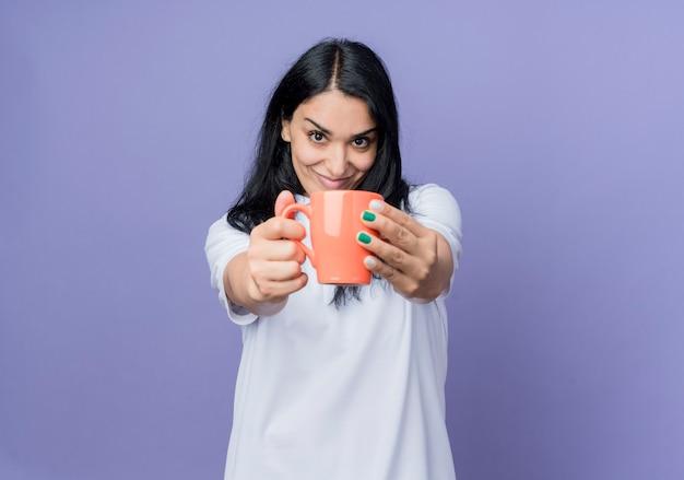 La giovane ragazza caucasica castana soddisfatta tiene fuori la tazza isolata sulla parete viola