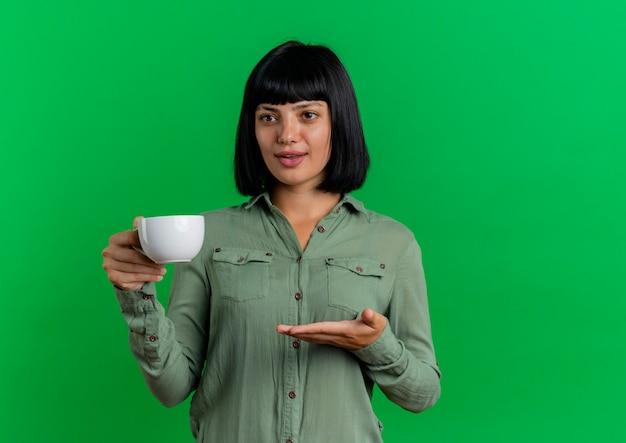 La giovane ragazza caucasica castana piacevole tiene e indica con la mano alla tazza