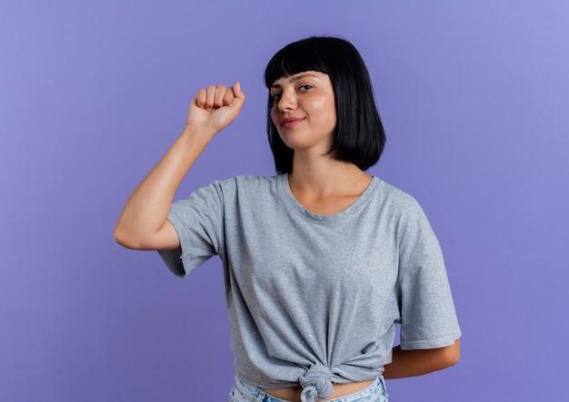 Довольная молодая брюнетка кавказская девушка держит кулак, глядя в сторону, изолированную на фиолетовом фоне с копией пространства