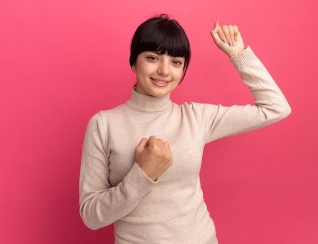 満足している若いブルネットの白人の女の子は拳を保ちます