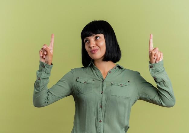 Довольная молодая брюнетка кавказская девушка смотрит и указывает вверх двумя руками, изолированными на оливково-зеленом фоне с копией пространства