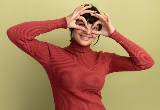 満足している若いブルネットの白人の女の子は指を通してカメラを見る
