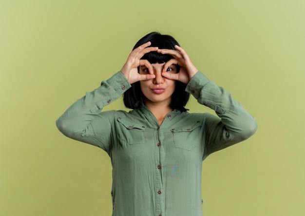 Lieta giovane ragazza caucasica bruna guarda attraverso le dita isolate su sfondo verde oliva con spazio di copia