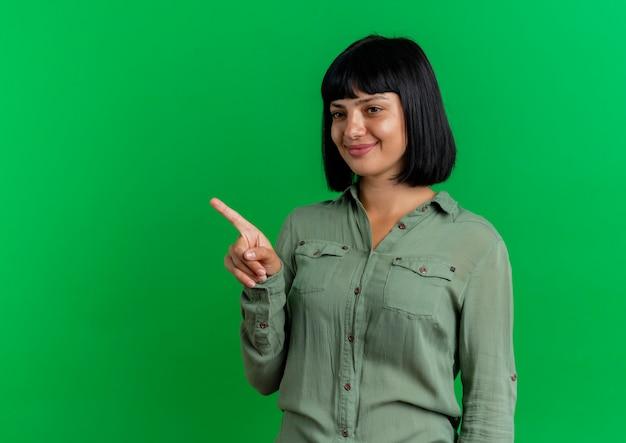 La giovane ragazza caucasica castana soddisfatta indica ed esamina il lato isolato su fondo verde con lo spazio della copia