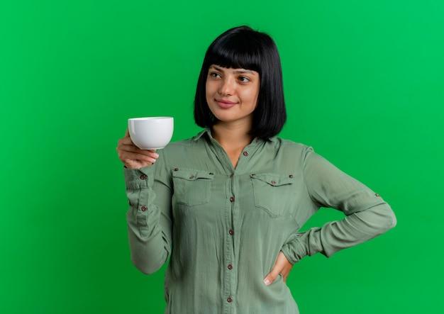La giovane ragazza caucasica castana soddisfatta mette la mano sulla tazza della tenuta della vita isolata su fondo verde con lo spazio della copia