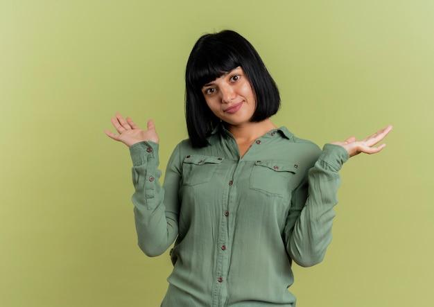 La giovane ragazza caucasica castana soddisfatta sta con le mani aperte isolate su fondo verde oliva con lo spazio della copia