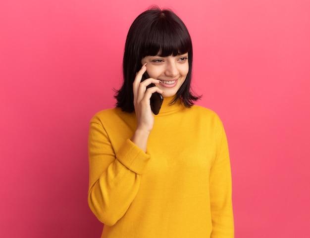 분홍색 측면을보고 전화에 만족 된 젊은 갈색 머리 백인 여자 회담
