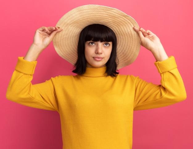 Довольная молодая брюнетка кавказская девушка в пляжной шляпе смотрит вверх