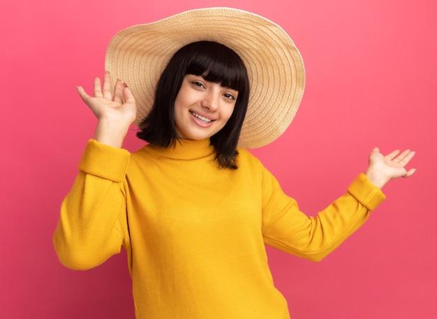 ピンクの上げられた手でビーチ帽子をかぶって満足している若いブルネットの白人の女の子