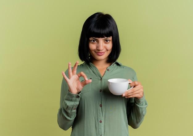 La giovane donna caucasica castana soddisfatta tiene il segno giusto della mano di gesti e della tazza isolato su fondo verde oliva con lo spazio della copia