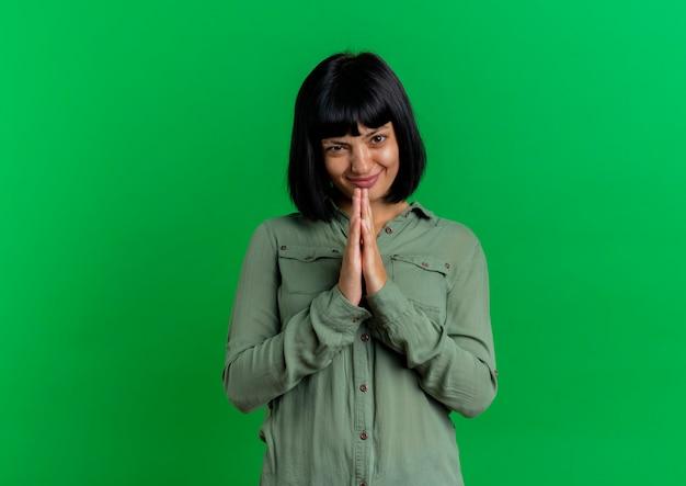 Lieta giovane donna bruna caucasica tiene le mani insieme isolato su sfondo verde con spazio di copia