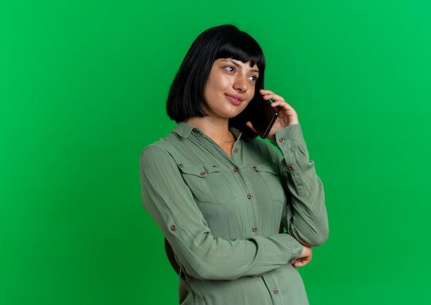 Lieta giovane donna caucasica bruna sta lateralmente parlando al telefono e guardando il lato isolato su sfondo verde con spazio di copia