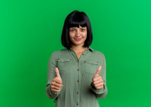 満足している若いブルネット白人女性は、コピースペースで緑の背景に分離された両手で親指を立てる