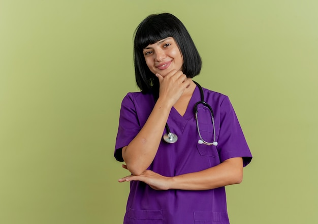 청진 제복을 입은 기쁘게 젊은 갈색 머리 여성 의사는 복사 공간 올리브 녹색 배경에 고립 된 카메라를보고 턱에 손을 넣습니다