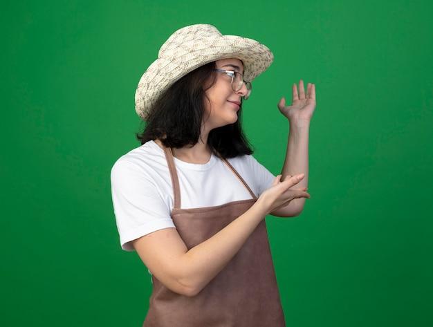 光学メガネと制服を着た若いブルネットの女性の庭師は、緑の壁に隔離された手でガーデニング帽子を指しています