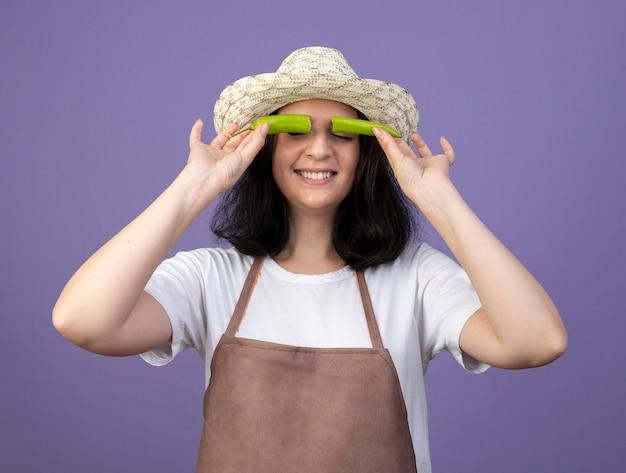 원예 모자를 쓰고 제복을 입은 기쁘게 젊은 갈색 머리 여성 정원사는 보라색 벽에 고립 된 고추의 절반으로 눈을 다룹니다.