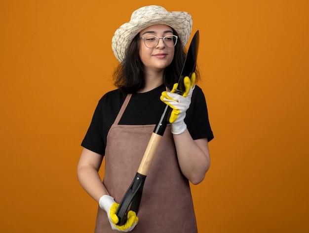 Lieta giovane giardiniere femminile brunetta in occhiali ottici e in uniforme che indossa guanti e cappello da giardinaggio tenendo e guardando la vanga isolata sulla parete arancione