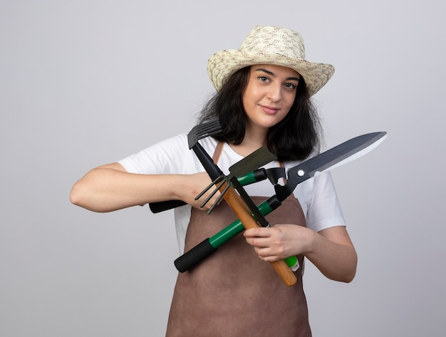 Pleased young brunette female gardener in uniform wearing gardening hat holds gardening tools isolated on white wall with copy space