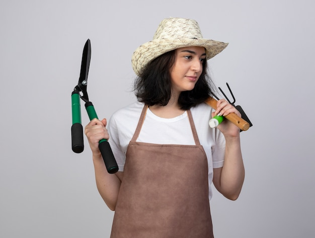 Pleased young brunette female gardener in uniform wearing gardening hat holds gardening tools looking at side isolated on white wall