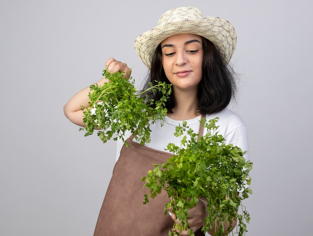 Il giardiniere femminile giovane brunetta soddisfatto in cappello da giardinaggio d'uso uniforme tiene ed esamina il coriandolo isolato sulla parete bianca