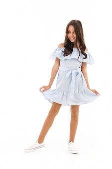 Доволен молодая брюнетка девушка в платье позирует на белом