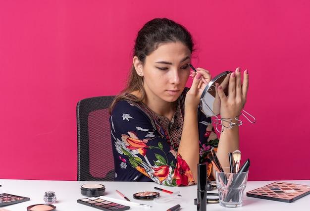 행복한 어린 브루네트 소녀가 화장 도구를 들고 테이블에 앉아 메이크업 브러쉬를 들고 분홍색 벽에 격리된 거울을 보고 복사 공간이 있는 거울을 보고 있습니다.