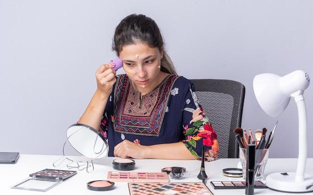 Довольная молодая брюнетка девушка сидит за столом с инструментами для макияжа, применяя тональный крем с губкой, глядя в зеркало