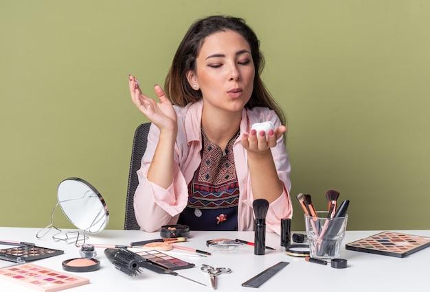 Довольная молодая брюнетка девушка сидит за столом с инструментами для макияжа и дует мусс для волос, изолированные на оливково-зеленой стене с копией пространства