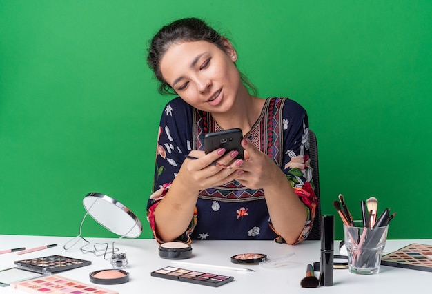 Довольная молодая брюнетка девушка сидит за столом с инструментами для макияжа, держа и глядя на телефон, изолированный на зеленой стене с копией пространства