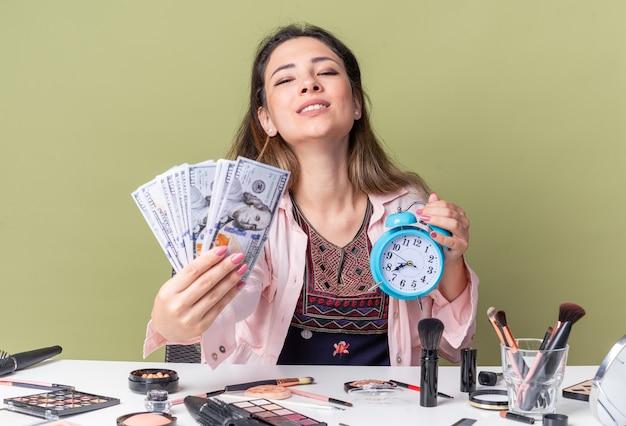 Довольная молодая брюнетка девушка сидит за столом с инструментами для макияжа, держит деньги и будильник, изолированные на оливково-зеленой стене с копией пространства