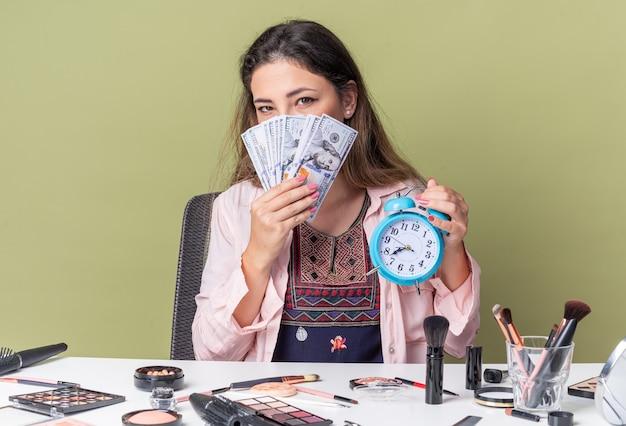 Довольная молодая брюнетка девушка сидит за столом с инструментами для макияжа, держит деньги и будильник