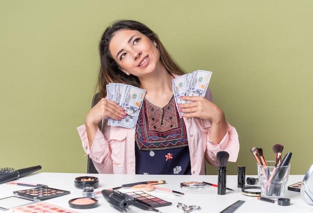 Довольная молодая брюнетка девушка сидит за столом с инструментами для макияжа, держит деньги и смотрит вверх изолированно на оливково-зеленой стене с копией пространства