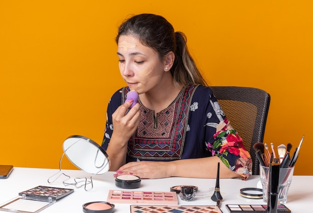 Lieta giovane ragazza bruna seduta al tavolo con strumenti per il trucco che applica il fondotinta con una spugna guardando lo specchio