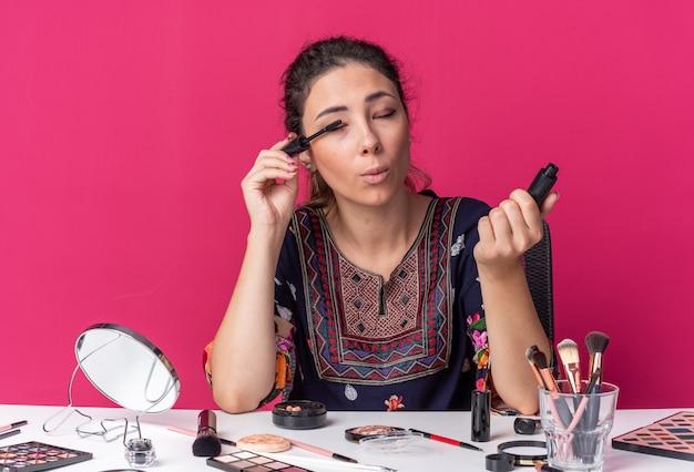 Felice giovane ragazza bruna seduta al tavolo con strumenti per il trucco che applica mascara isolato su parete rosa con spazio per le copie