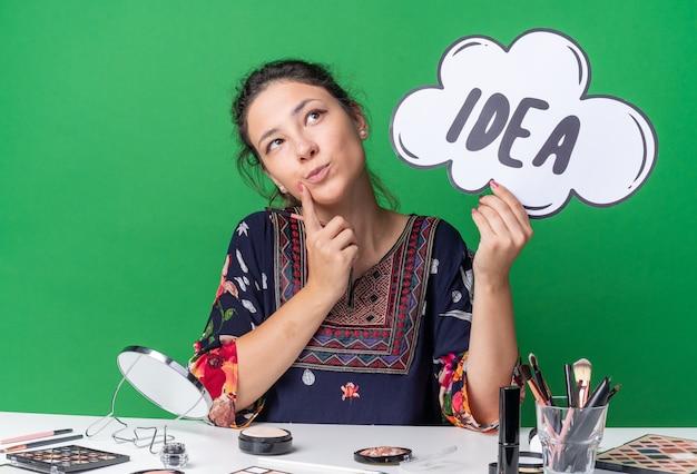 Felice giovane ragazza bruna seduta al tavolo con strumenti per il trucco che tiene in mano una bolla di idee e un pennello per il trucco che guarda in alto