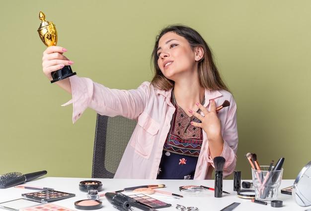 Felice giovane ragazza bruna seduta al tavolo con strumenti per il trucco che tiene il pennello per il trucco e guarda la tazza del vincitore isolata sul muro verde oliva con spazio per le copie