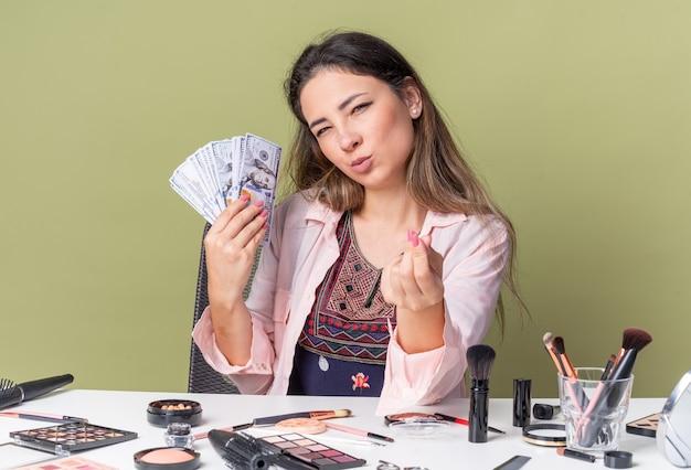 Lieta giovane ragazza bruna seduta al tavolo con strumenti per il trucco in possesso di denaro e gesticolando segno di denaro