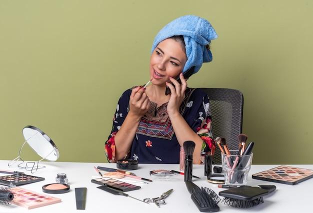 Довольная молодая брюнетка с обернутыми волосами в полотенце сидит за столом с инструментами для макияжа, разговаривает по телефону, применяя блеск для губ, изолированную на оливково-зеленой стене с копией пространства