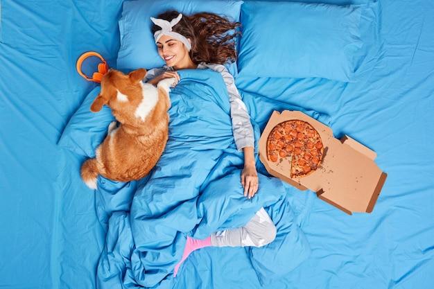 Довольная молодая брюнетка играет с собакой, одетой в удобную пижаму, ленившись встать с постели, ест вкусную пиццу, забывает обо всей работе, расслабляется вместе с любимым питомцем после хорошего сна