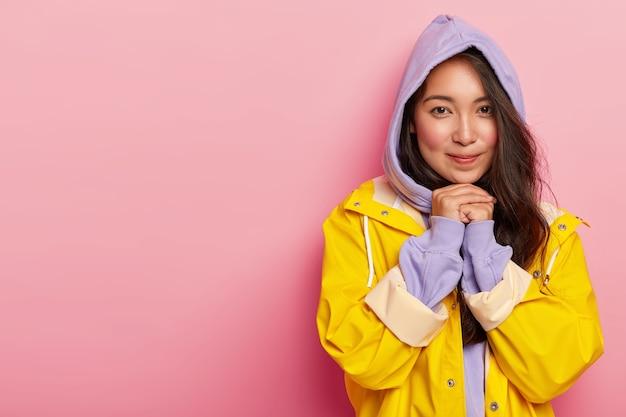 満足している若いブルネットの女性は、フーディ、黄色の防水レインコートとカジュアルなスウェットシャツを着て、あごの下で手を一緒に押し続けます