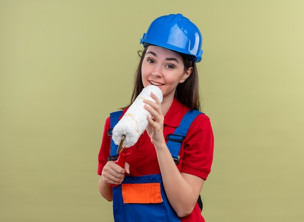 Pleased young builder girl with blue safety helmet holds paint roller like mic with both hands on isolated green background