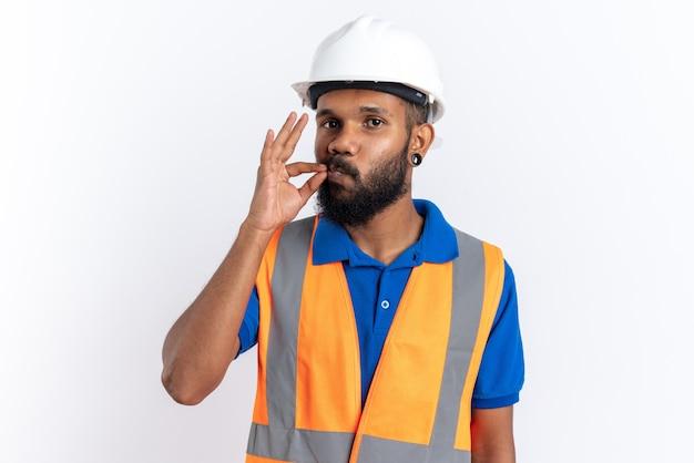 복사 공간이 있는 흰색 벽에 격리된 완벽한 제스처를 하는 안전 헬멧을 쓴 제복을 입은 젊은 건축업자