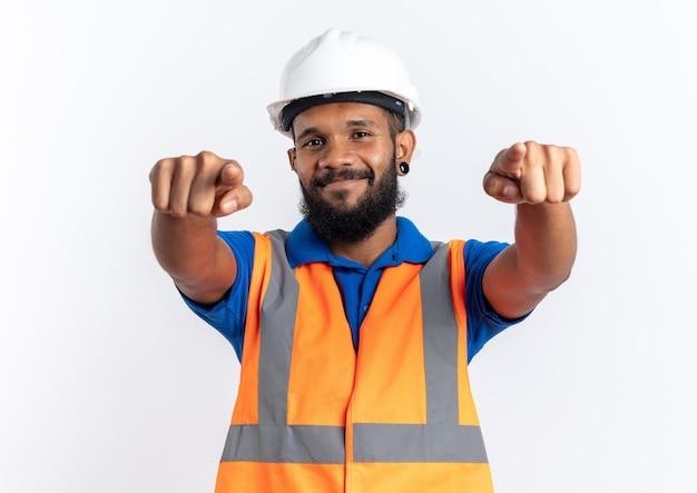복사 공간이 있는 흰 벽에 격리된 두 손으로 앞을 가리키는 안전 헬멧을 쓴 제복을 입은 젊은 건축업자