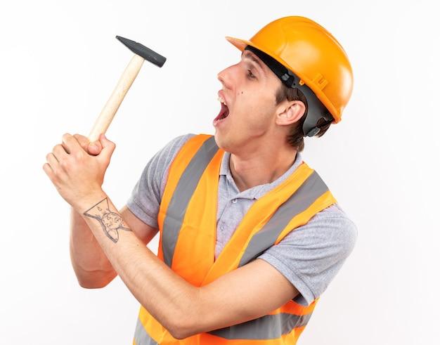 Felice giovane costruttore in uniforme che tiene in mano e guarda il martello
