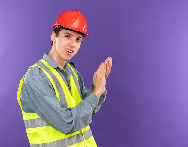 Pleased  young builder man in uniform showing handshakes gesture isolated on blue wall with copy space