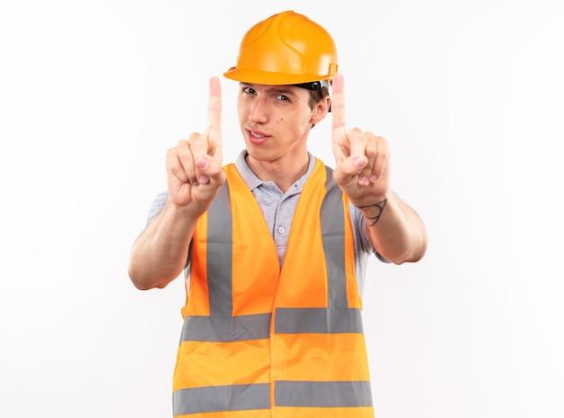 Felice giovane costruttore in uniforme che ne mostra uno isolato sul muro bianco