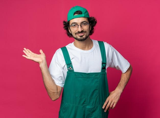 Felice giovane costruttore che indossa l'uniforme con il berretto che allarga la mano