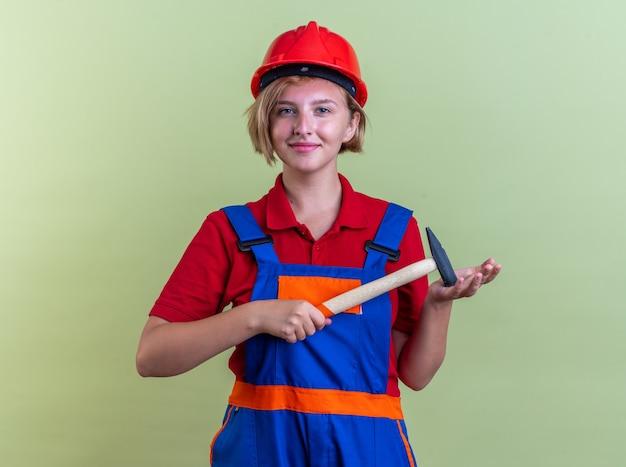 オリーブグリーンの壁に分離されたハンマーを保持している制服を着た若いビルダーの女性を喜ばせる